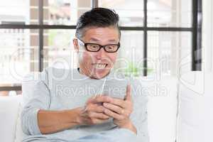 Mature Asian man getting excited while using smartphone