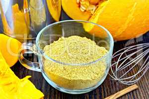 Flour pumpkin in glass cup with mixer on board