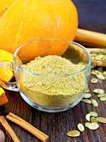 Flour pumpkin in glass cup with seeds on board