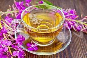 Tea from fireweed in glass cup on board