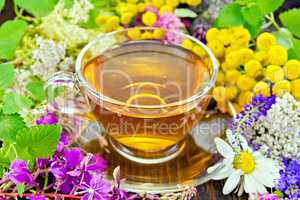 Tea from flowers in glass cup on dark board