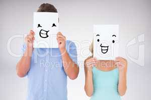 Composite image of young couple holding pages over their faces