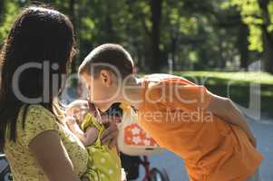 Women, brother and baby in a park.
