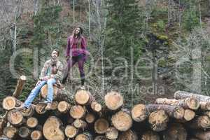 Young woman and men on wood logs