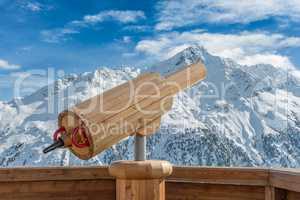 Aussichtspunkt mit Fernrohr aus Holz mit verschneiter Berglandschaft im Hintergrund