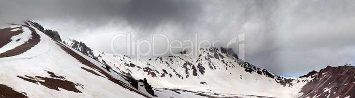 Panorama of snowy mountains before rain