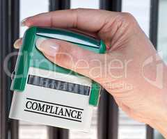 Compliance Stamp with female hand in the office