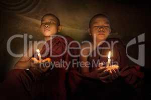 Buddhist novices praying with candlelight