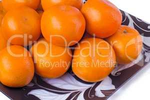 Large ripe tangerines in a glass dish on a white background.