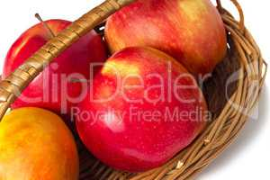Big apples in wattled to a basket on a white background