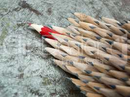Close up of identical graphite pencils and one red leading crayo