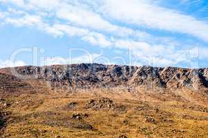 Rocky dry yellow cliff ridge against light blue sky