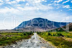 Rocky gravel path leading to mountain under clouds and sky