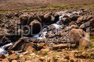Stream flowing and splashing among bare rocky landscape