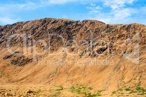 Rocky dry yellow cliff ridge with eroded channels