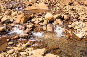 Clear shallow water flowing and splashing on bare rocks