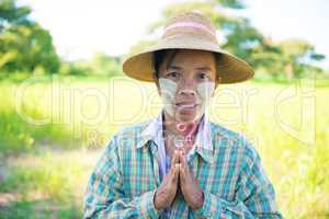 Traditional mature Asian female farmer greeting