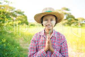 Traditional young Myanmar female farmer greeting