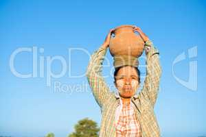Mature Asian traditional female farmer carrying clay pot on head