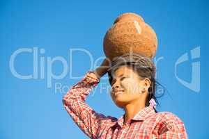 Young Asian traditional farmer carrying clay pot on head