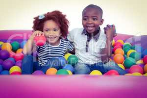 Cute children in ball pool holding balls