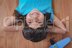 Smiling girl laying on the floor wearing aviator glasses and hat