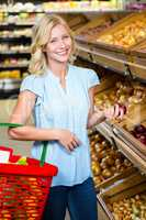Smiling woman holding basket and red onion