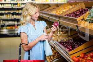 Doubtful woman looking onion