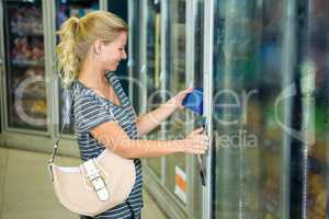 Smiling woman taking product from the fridge
