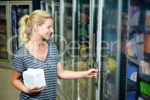 Smiling woman closing fridge and holding product