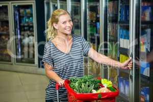 Smiling woman with shopping basket opening fridge