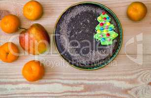 Chocolate cake and fruit: apples and tangerines.