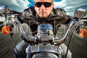Funny Biker in sunglasses and leather jacket racing on mountain