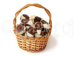 Chocolates in a wattled basket on a white background.