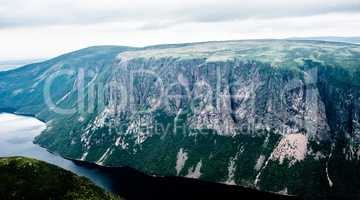 Large steep cliffs and plateau forming fjord under overcast sky