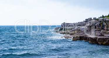 Rocky coastline with waves splashing under overcast sky