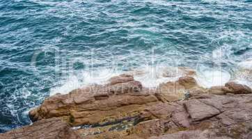 Splashing ocean waves crashing against bare rocks