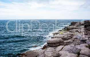 Horizon and rocky coastline with waves splashing under cloudy sk