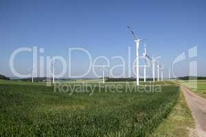 Windmill generator in wide yard / Yard of windmill power generatorunder blue sky, shown as energy industry concept.