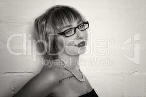 Frau mit Brille steht vor einer weißen Wand