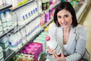 Smiling woman holding milk bottle