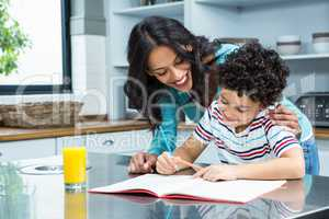 Kind mother helping her son doing homework