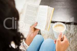 Over shoulder view of woman holding cup of coffee and book