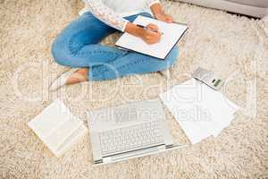 Above view of a woman writing note while using her laptop