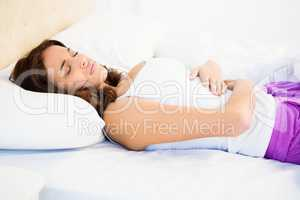Woman lying on her bed with a belly pain