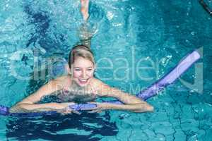 Fit woman doing aqua aerobics with foam rollers