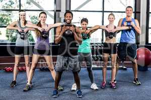 Class and instructor exercising with kettlebells