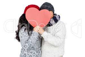 Couple hiding behind heart shape cardboard