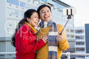 Older asian couple on balcony taking selfie
