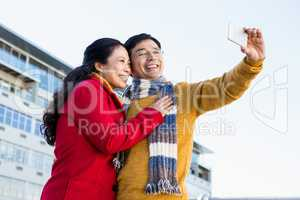 Older asian couple on balcony taking selfie